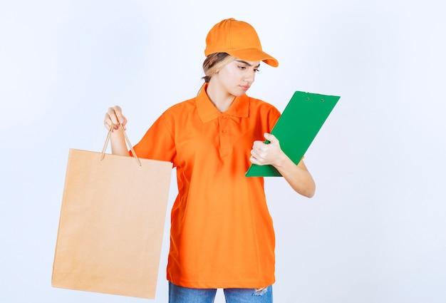 Kurierin in orangefarbener uniform, die eine einkaufstüte aus pappe hält und die grüne kundenliste überprüft