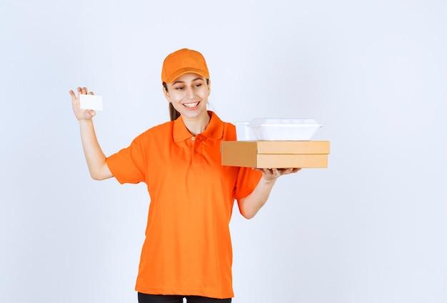 Kurierin in orangefarbener uniform, die eine pappschachtel und eine plastikbox zum mitnehmen hält, während sie ihre visitenkarte vorlegt