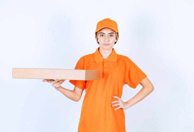 Kurierin in orangefarbener uniform, die einen karton liefert