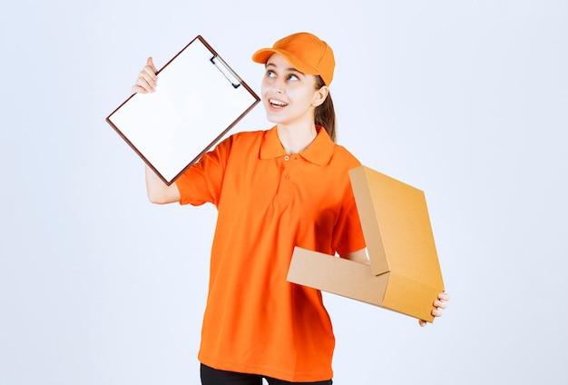 Kurierin in orangefarbener uniform, die einen offenen karton hält und um eine unterschrift bittet