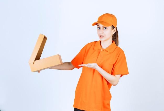 Kurierin in orangefarbener uniform, die einen offenen karton hält und verwirrt und nachdenklich aussieht.