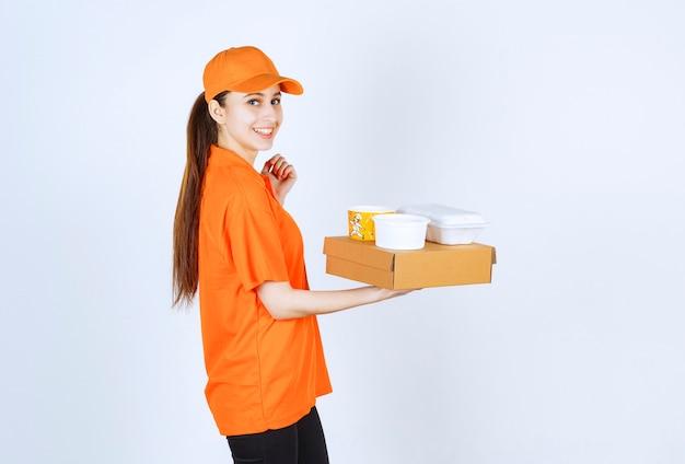 Kurierin in orangefarbener uniform mit einem karton, einer plastikbox zum mitnehmen und einem gelben nudelbecher