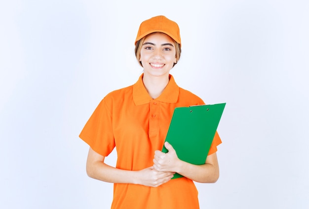 Kurierin in orangefarbener uniform mit grüner kundenliste