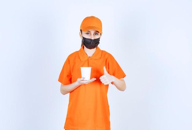 Kurierin in orangefarbener uniform und schwarzer maske, die ein getränk zum mitnehmen hält und den geschmack genießt
