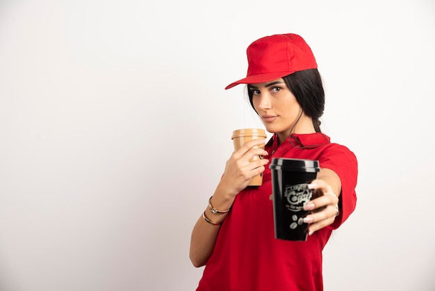 Kurierin in roter uniform, die eine tasse kaffee verschenkt. hochwertiges foto