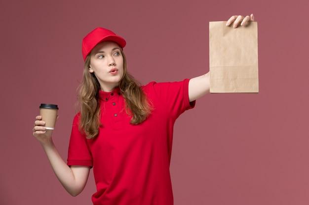 Kurierin in roter uniform, die kaffeetasse mit lebensmittelverpackung auf rosa, einheitlichem dienstlieferauftrag hält