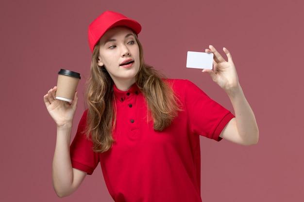 Kurierin in roter uniform, die weißen kartenkaffee auf hellrosa, dienstuniform-dienstarbeiterzustellung hält