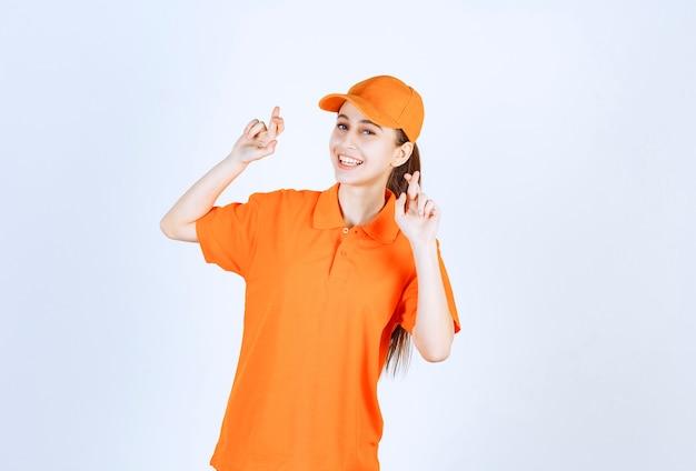 Kurierin mit orangefarbener uniform und mütze