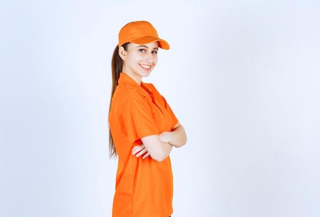 Kurierin trägt orangefarbene uniform und mütze, die die arme verschränkt und einen professionellen look verleiht