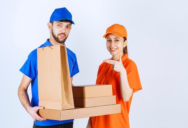 Kurierjunge und -mädchen in den blauen und gelben uniformen, die pappkartons und einkaufspakete halten.