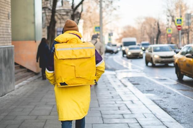 Kurierlieferant mit riesigem rucksack zu fuß b Premium Fotos