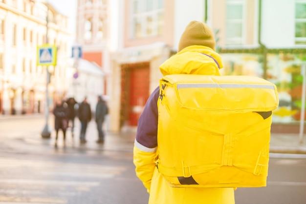 Kurierlieferant mit riesigem rucksack zu fuß b