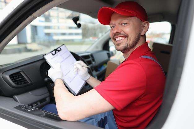 Kuriermann füllt dokumente in zwischenablage im auto aus