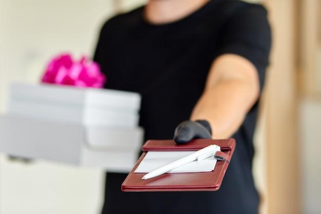 Kuriermann kontaktlose lieferung präsentiert, geschenkbox während einer coronavirus-epidemie.