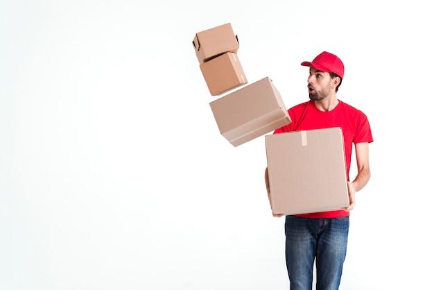 Kuriermann lässt die paketpostkästen fallen und schaut ängstlich