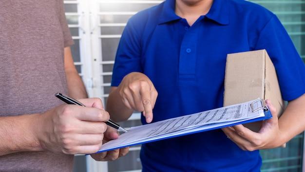 Kurierzusteller, der das paketpaket aus pappe überprüft oder hält, um es zu liefern