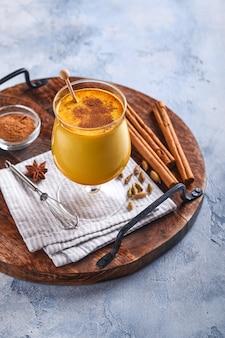 Kurkuma-goldener milchlatte mit zimtstangen und honig. gesundes ayurvedisches getränk. trendiges asiatisches natürliches detox-getränk mit gewürzen für veganer. platz kopieren.