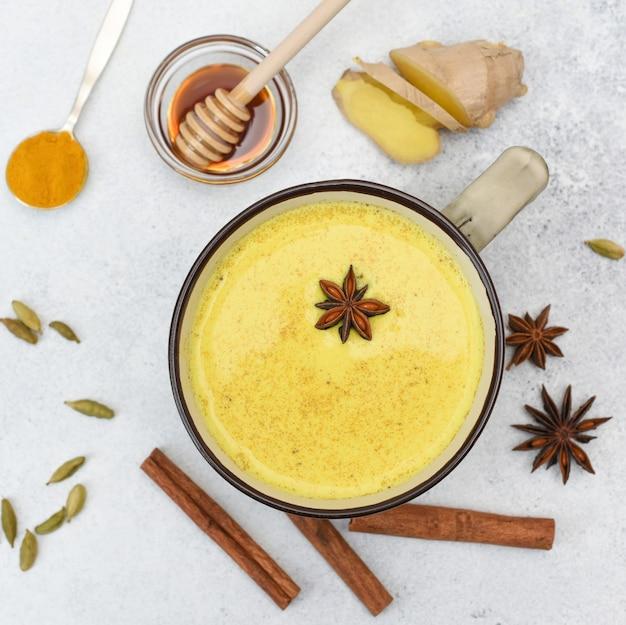 Kurkuma latte draufsicht. goldene milch in einer tasse mit sternanis und gewürzen. kurkuma, zimt, ingwer, honig, sternanis, kardamom.