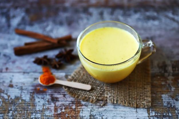 Kurkuma-milch mit gewürzen in einer tasse. goldene kurkuma-milch. indisches gesundheitsgetränk. selektiver fokus.
