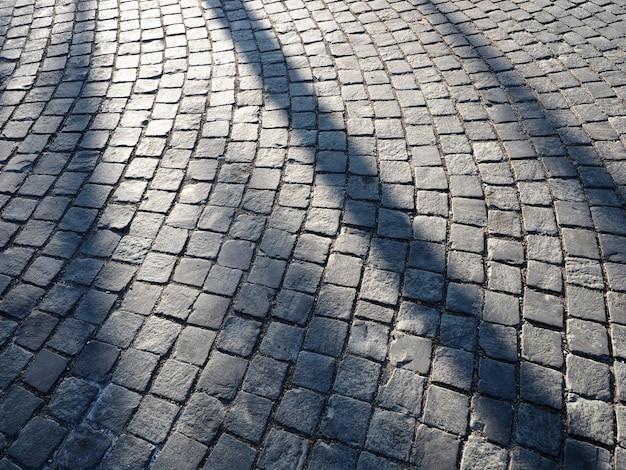 Kurvengrauer ziegelboden mit sonnenlicht und schatten