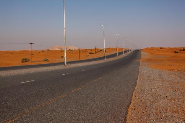 Kurvenreiche schwarze asphaltstraße durch sanddünen