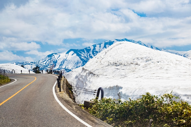 Kurvenreiche straßen mit schnee, bergen und dem blauen himmel in japan