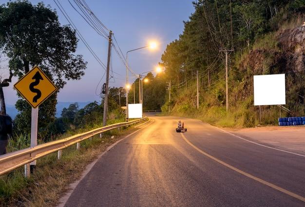 Kurvenstraßenbeleuchtung auf dem berg in der abenddämmerung