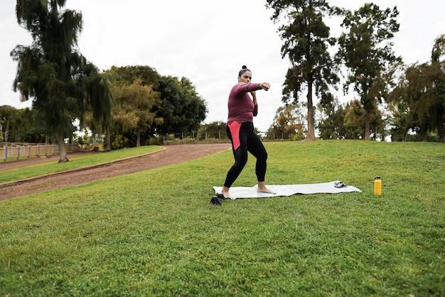Kurvige frau, die workout-boxroutine im freien am stadtpark tut - fokus auf gesicht