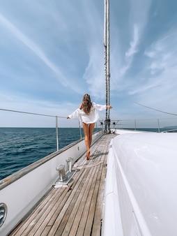 Kurvige frau in einem roten badeanzug, die auf der vorderseite des bootsdecks auf türkisblauer meeresoberfläche steht