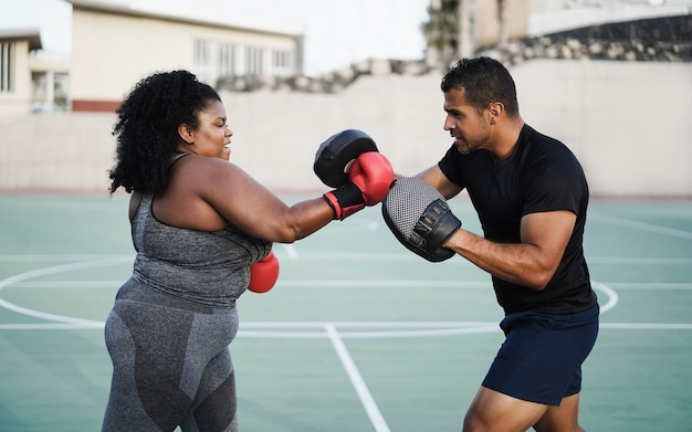 Kurvige frau und personal trainer beim boxtraining im freien - hauptaugenmerk auf dem gesicht des trainers