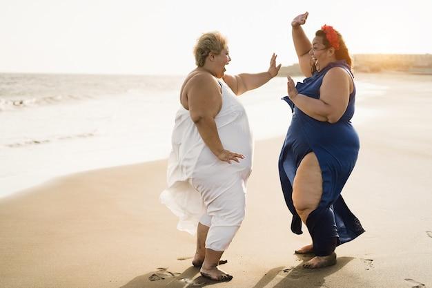 Kurvige freundinnen tanzen am strand und amüsieren sich im sommerurlaub - fokus auf gesichtern