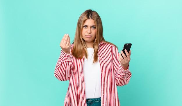 Kurvige hübsche blonde frau, die eine capice- oder geldgeste macht, ihnen sagt, dass sie bezahlen und ein smartphone halten sollen