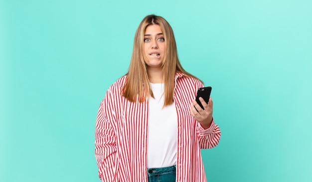 Kurvige hübsche blonde frau, die verwirrt und verwirrt aussieht und ein smartphone hält