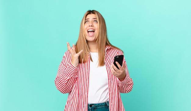 Kurvige hübsche blonde frau, die verzweifelt, frustriert und gestresst aussieht und ein smartphone hält