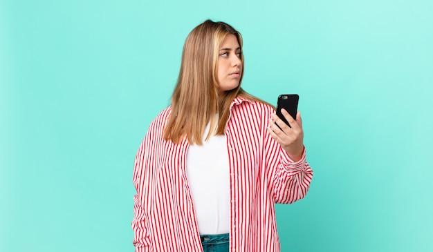 Kurvige hübsche blonde frau in der profilansicht, die nachdenkt, sich vorstellt oder träumt und ein smartphone hält