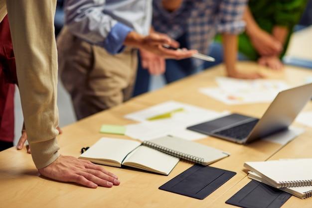 Kurz geschnitten von geschäftsleuten, die laptop verwenden, während sie im büro zusammenarbeiten