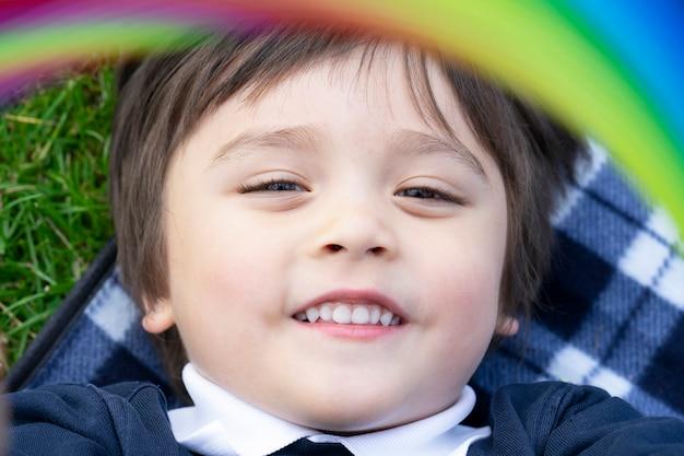 Kurz geschnittener glücklicher schuljunge, der auf picknickdecke auf gras liegt, nahes nahes kind mit lächelndem gesicht, offenes kurzes gesundes kind, das im frühling oder sommer im freien spielt