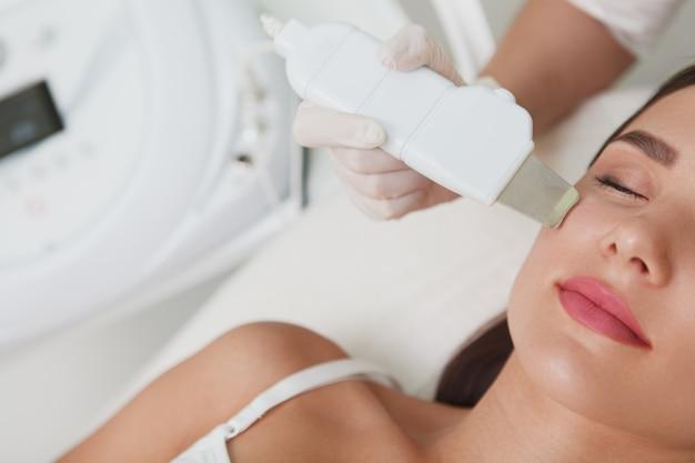 Kurzaufnahme einer frau, die ultraschall-gesichtsreinigungsbehandlung an der schönheitsklinik erhält