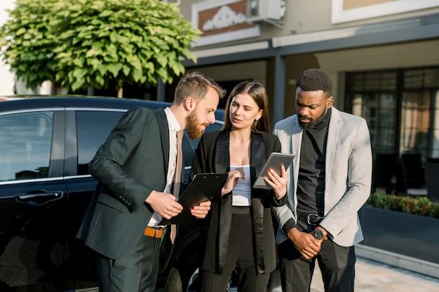 Kurze einweisung vor dem treffen. drei fröhliche junge multiethnische geschäftsleute, zwei männer und eine frau, die miteinander sprechen, während sie draußen in der nähe des schwarzen autos stehen. frau hält digitales tablet