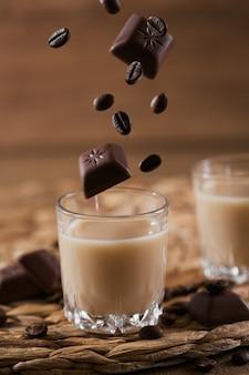 Kurze gläser irish cream liquor oder kaffeelikör mit fliegender schokolade und kaffeebohnen. winterfeiertagsdekorationen