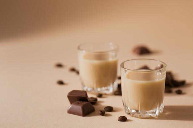 Kurze gläser irish cream liquor oder kaffeelikör mit schokolade und kaffeebohnen. winterfeiertagsdekorationen