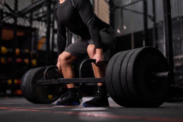 Kurzer bodybuilder-typ bereitet sich darauf vor, übungen mit langhantel in einem dunklen, modernen fitnesscenter oder fitnessstudio zu machen. die hand des bodybuilders hebt die langhantel und trainiert allein einen mann in sportlicher kleidung. seitenansicht