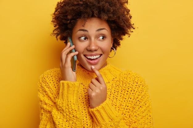 Kurzer schuss der glücklichen afroamerikanischen frau hat telefongespräch, hält gerät nahe ohr, fokussiert beiseite, gekleidet in warme kleidung, isoliert über gelbem hintergrund.