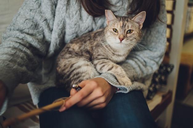 Kurzer schuss der jungen frau, die entzückende getigerte katze in den händen hält.