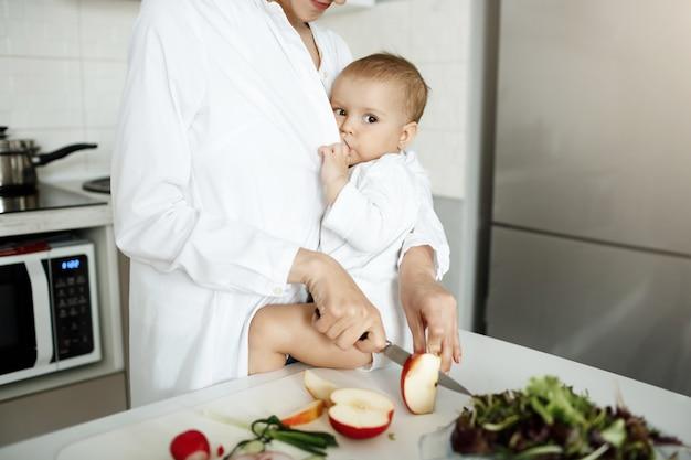 Kurzer schuss der mutter, die ihr baby stillt, während sie einen apfel schneidet