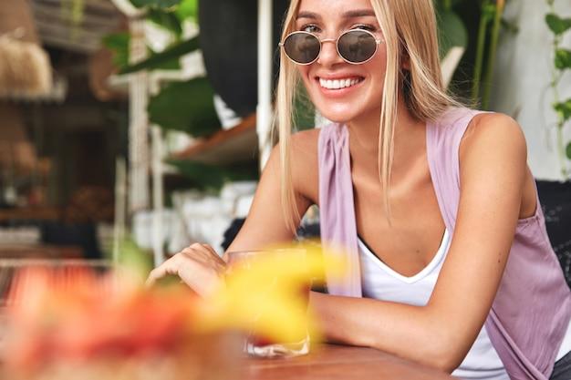 Kurzer schuss der schönen lächelnden frau trägt sonnenbrille und modische kleidung, ruht allein in der cafeteria mit leckerem getränk, hat glücklichen ausdruck. entspannte frauen ruhen im sommer in der gemütlichen bar