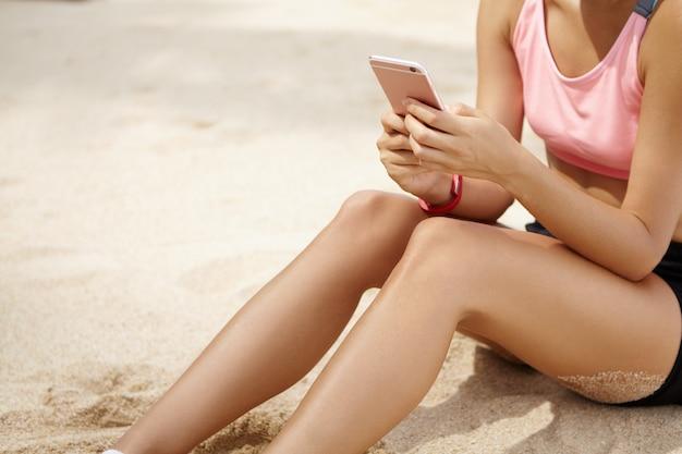 Kurzer schuss der sportlerin mit dem schönen athletischen körper, der auf sandstrand sitzt, nachdem übung am meer ausgeführt wird, internet surft und freunde über soziale netzwerke auf mobiltelefon mitteilt