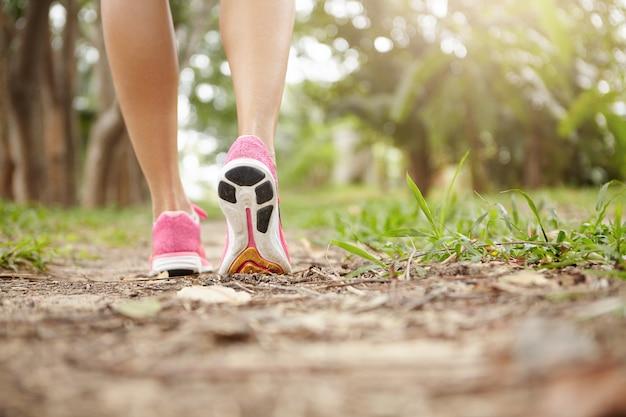Kurzer schuss des athletenmädchens in den rosa laufschuhen, die im wald am sonnigen tag wandern. passen sie die schlanken beine einer sportlichen frau während des jogging-trainings in turnschuhe. selektiver fokus auf sohle.