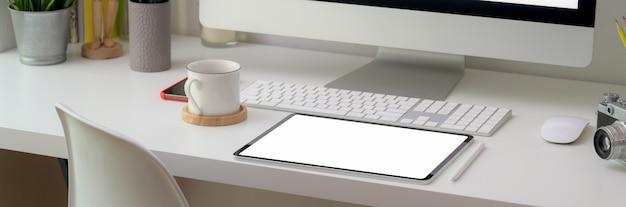 Kurzer schuss des bequemen schreibtischs mit tablett des leeren bildschirms und büromaterial