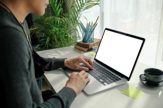 Kurzer schuss des freiberuflers des jungen mannes, der am laptop arbeitet.